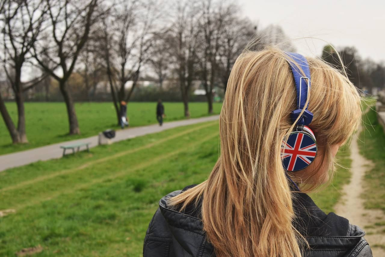 young lady UK headphones in park